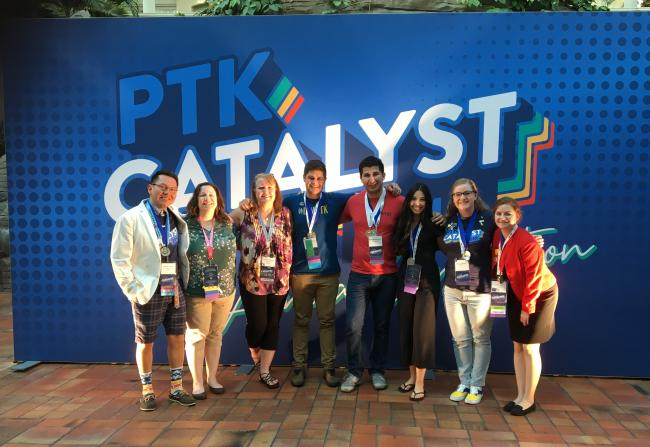 "Members of Alpha Upsilon Kappa stand in front of a sign that says ""PTK Catalyst."""