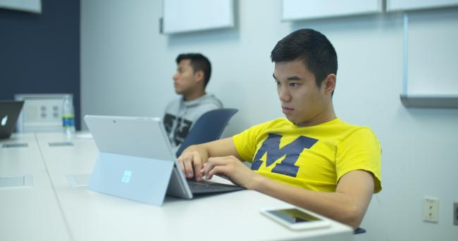 Student wearing a yellow University of Michigan t-shirt working with a laptop computer.