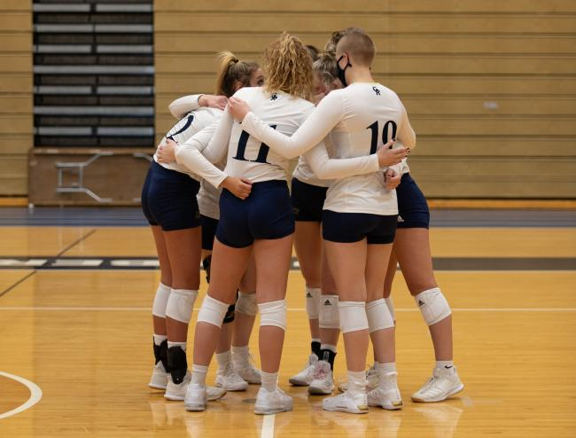 Volleyball players gather in a circle.
