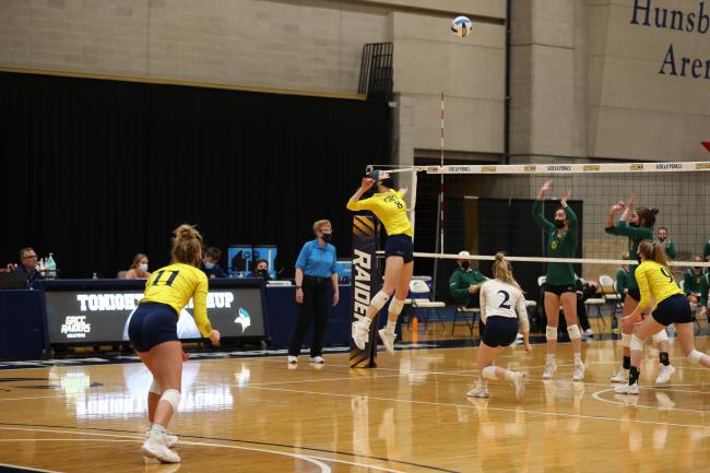 GRCC player leaping in front of the net for a spike.