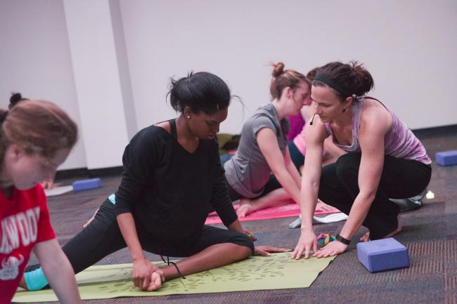 Jodi Gee works with a student during a yoga class.