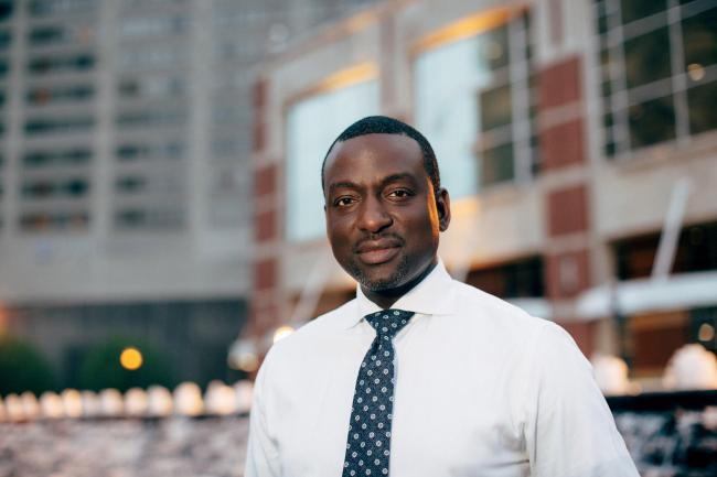 Dr. Yuseft Salaam, wearing a white shirt and blue tie.
