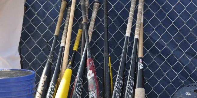 Baseball bats lean up against a chain-link fence.