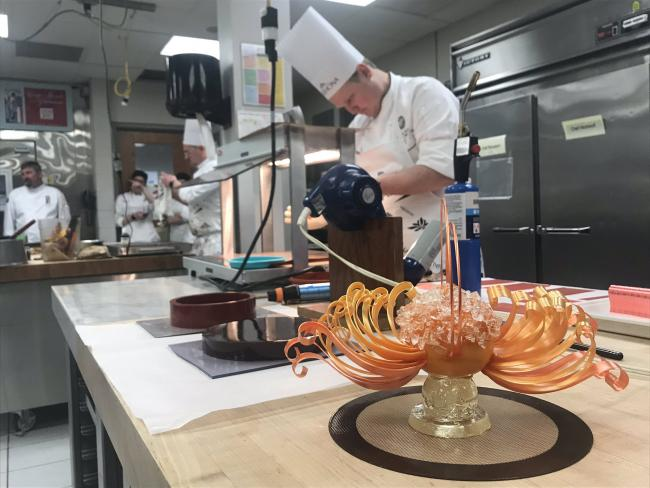 Chef preparing pulled sugar dessert in the competition.