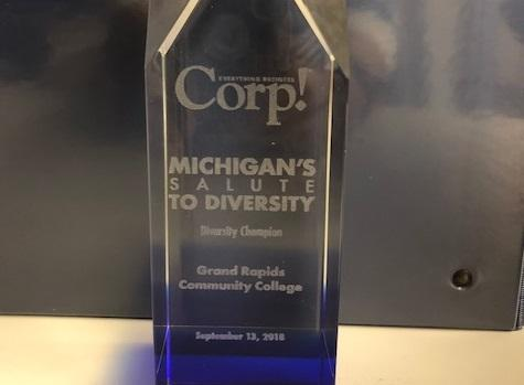 "Etched on the glass award, it says: ""Corp.! Michigan's Salute to Diversity. Diversity Champion. Grand Rapids Community College. September 13, 2018."""