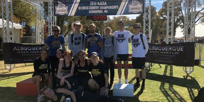 "Members of the men's and women's cross country team and coaches stand under a banner that says: ""2019 NJCAA DI Cross Country Championships, Albuquerque, NM."""