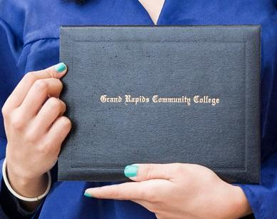 "A student holds a diploma case that says ""Grand Rapids Community College."""
