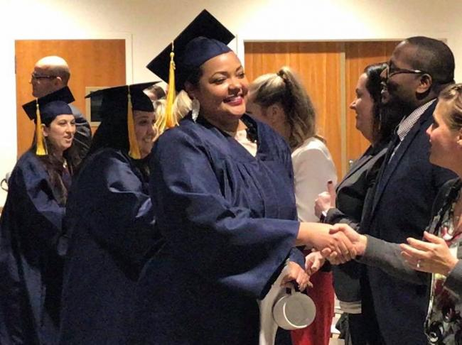 A Medical Assistant graduate shakes Amy Mansfield's hand.