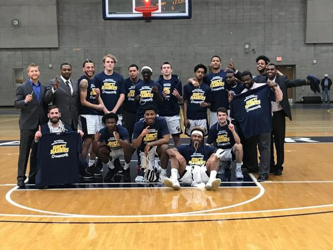 "The men's basketball team, all wearing T-shirts that say ""2019 MCCAA Western Conference Champions. GRCC Raiders,"" stand and sit under the basket at Ford Fieldhouse."