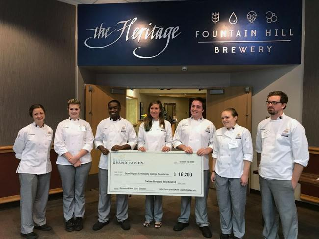 The seven 2017 Restaurant Week scholarship recipients hold a fake check from Experience Grand Rapids for $16,200. They stand under the entrance to the Heritage restaurant.