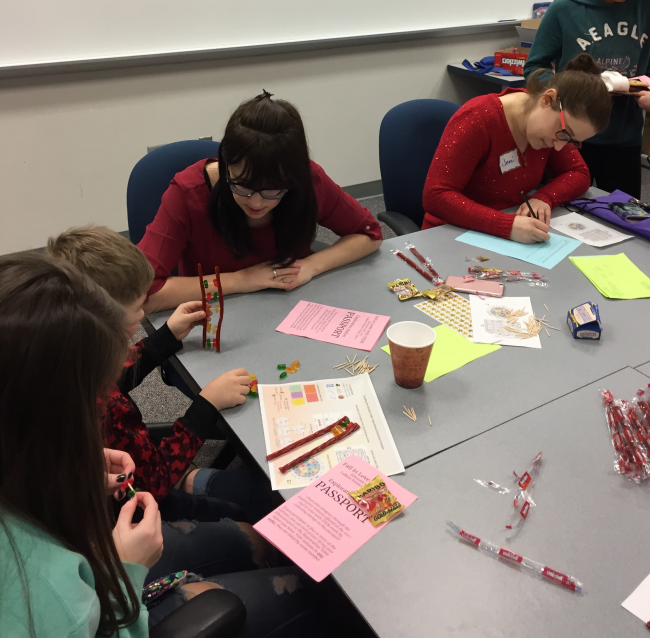 A GRCC student, seated at a table, watches middle schoolers create DNA strands from Twizzlers and gummies.