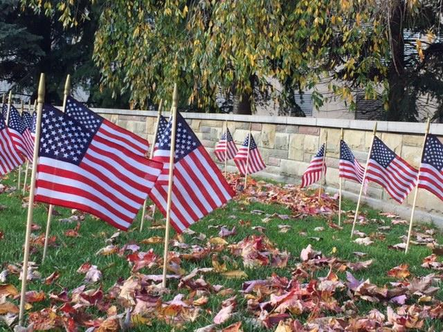 Small U.S. flags are planted in the ground near GRCC's Veterans Memorial.