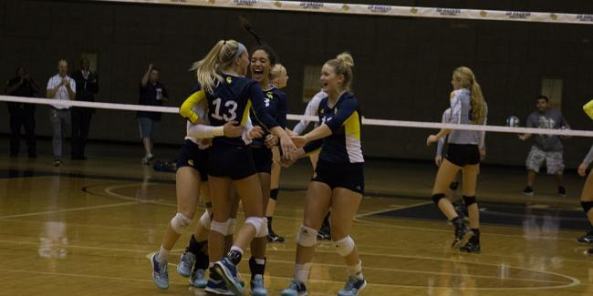 Members of the volleyball team hug in front of the net.