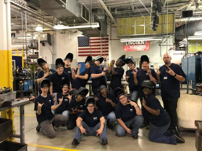 An instructor and 15 welding students, all wearing Metallica Scholars T-shirts and welding helmets, pose in Tassell M-TEC's welding facility.