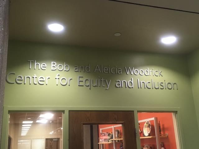 "A sign above a door says: ""The Bob and Aleicia Woodrick Center for Equity and Inclusion."""