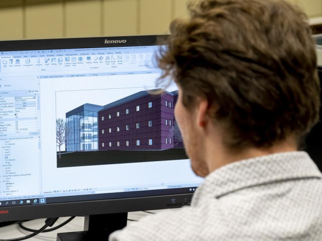 A student designing a building on a computer