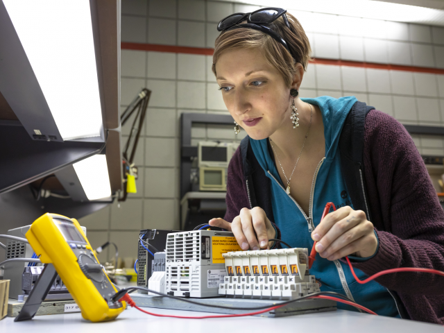Woman working on mechatronics project at GRCC.