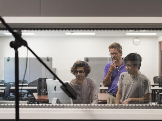 Three students in a sound booth working with recording equipment