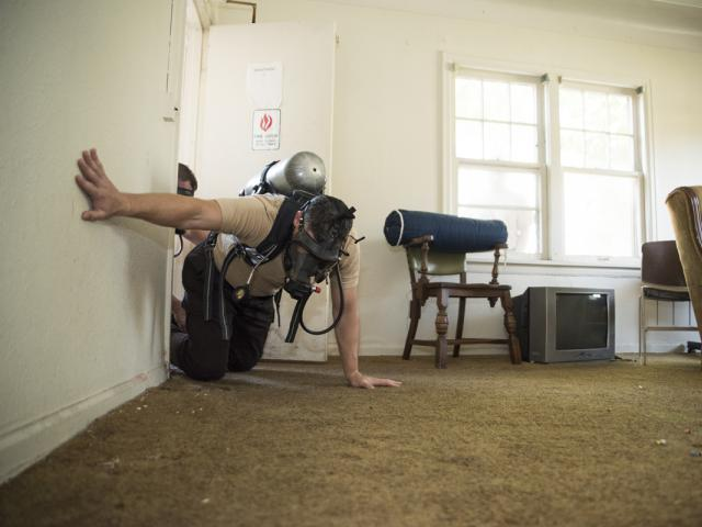 Sheriff's Corrections Academy student crawling in a house with a gas mask on.