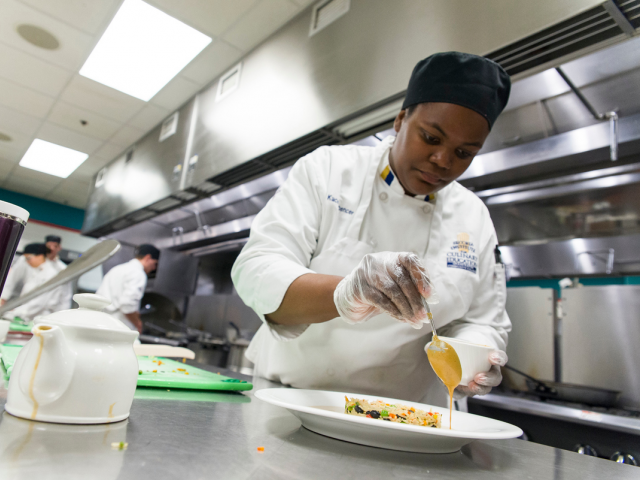 student sauces a plate in a culinary class.