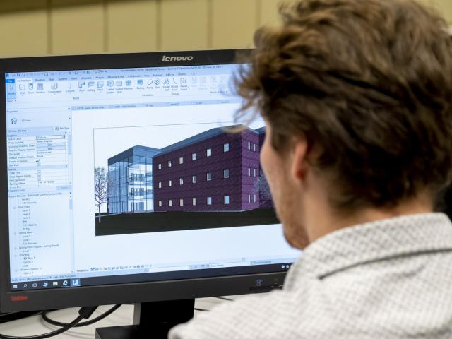Student uses CAD program to design buildings.